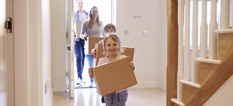 Family carrying boxes into new home on moving day - shutterstock_451241899