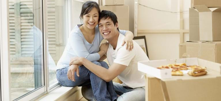 Asian couple surrounded by moving boxes - shutterstock_221297176.jpg