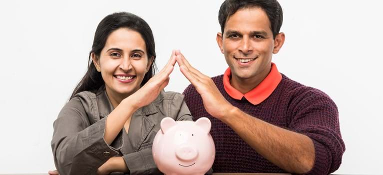 Indian Asian smart and young couple saving money in Piggy Bank for buying a dream Home concept - shutterstock_704741464.jpg