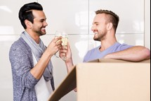 Smiling couple toasting with champagne while unpacking cardboard shutterstock_371424241.jpg